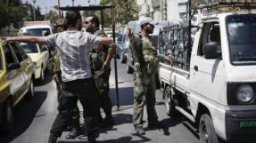 The regime's checkpoints take out identity cards from civilians to force them to elect Al-Assad